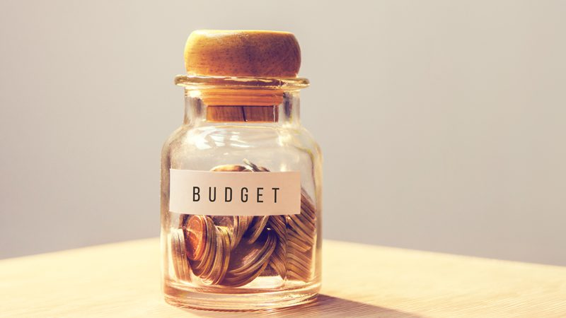 A jar of coins with a label saying BUDGET