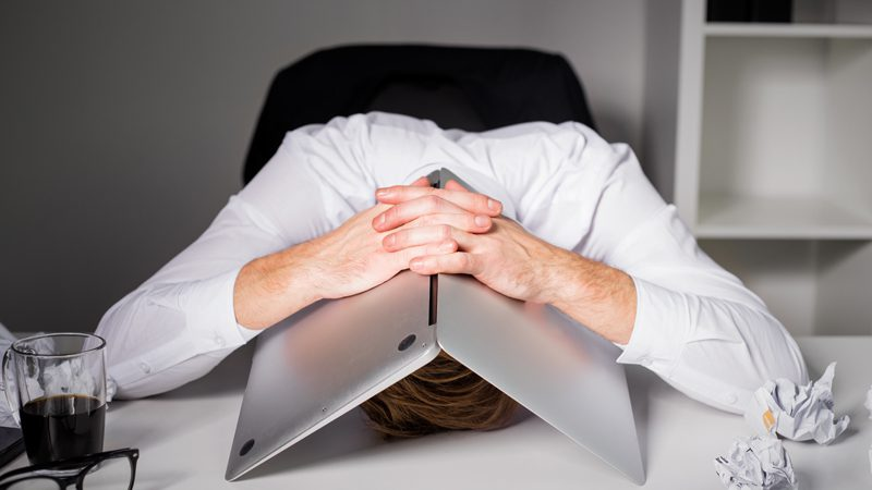 Man with his head under a laptop computer